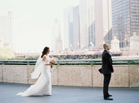 Bride sneaks up behind groom in tuxedo during first look in Chicago