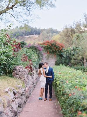 bride in short knee length wedding dress light blue heels and open back with groom in navy suit