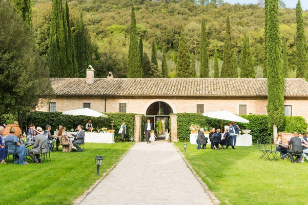 destination wedding reception in italy parasols and wrought iron outdoor garden furniture lawn trees