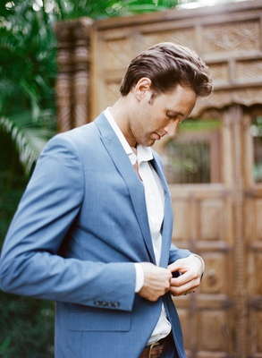 Groom in relaxed attire no tie white button down shirt light blue suit jacket for destination weddin