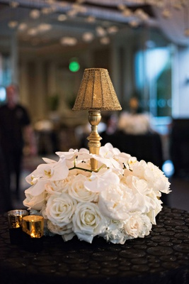 cocktail hour flower arrangement white rose orchid around gold candlestick gold beaded shade