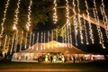 strings of twinkle lights hang from tree outside of tented reception