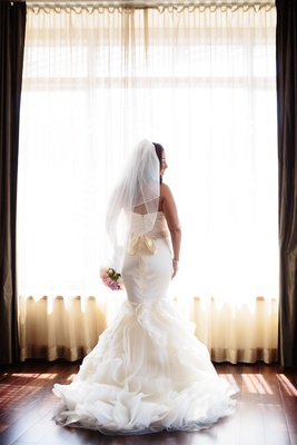 Bride in a fit-and-flare Vera Wang dress with ruffled skirt, beaded sash, ruching on bodice, veil