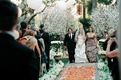 Bride walks down rose petal aisle runner with parents