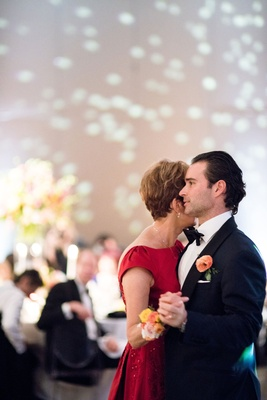 Groom in tuxedo and bow tie dancing with mother of groom in red dress corsage