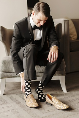 groom with black socks and white polka dots, glittery gold shoes