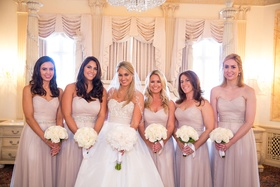 Bride in strapless Reem Acra wedding dress with bridesmaids in champagne pink bridesmaid dresses