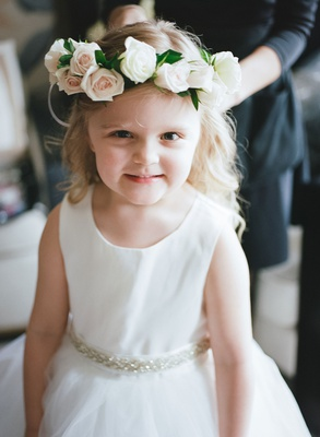flower girl in white dress curled blonde hair flower grown with pink white roses and greenery