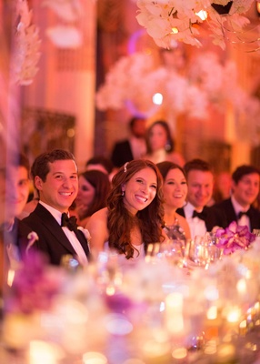 Bride and groom smiling with guests at head table during reception toasts laughing smiling