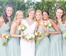 Bride in a lace Watters dress and bridesmaids in different seafoam J.Crew dresses