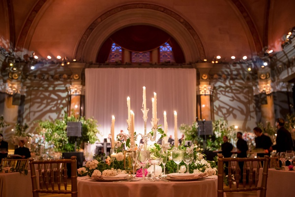 Wedding reception sweetheart table facing dance floor with candelabra taper candles gold chairs
