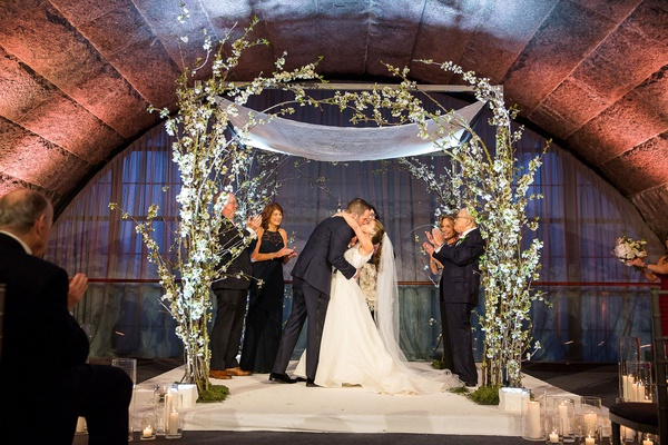 Wedding ceremony granite arch greenery white flower chuppah tallit bride and groom parents jewish