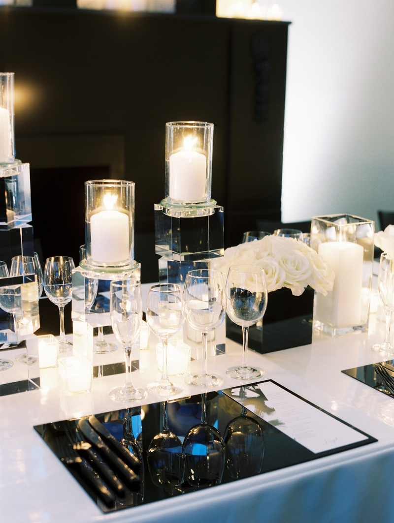 modern, chic black and white wedding tablescape with white linens and gunmetal lucite placemat