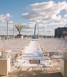 Gateway Arch in background, white aisle runner lined with white and pink flowers, ghost chairs, sign