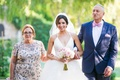 a bride in a tulle ball gown holding a blush and ivory bouquet walks down aisle escorted parents