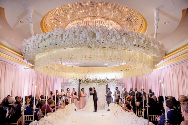 wedding ceremony large white flower circle over dance floor kiss newlyweds ballroom ceremony candles