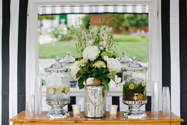 Silver water dispensers serving drinks at wedding ceremony with mercury glass vase flowers