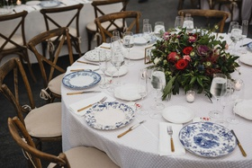 round wedding reception table white linen wood chair low centerpiece fall colors blue white china