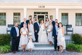 bride in striped hayley paige wedding dress with groom in navy suit, bridal party on porch