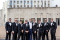 groom in navy tuxedo, groomsmen in classic black tux, groom and groomsmen in sunglasses
