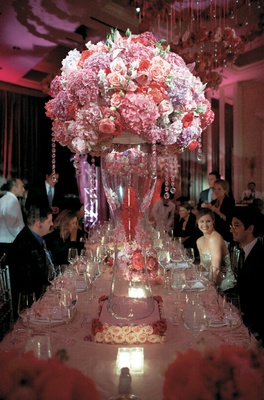 tall glass vase with pink flowers and crystals on top