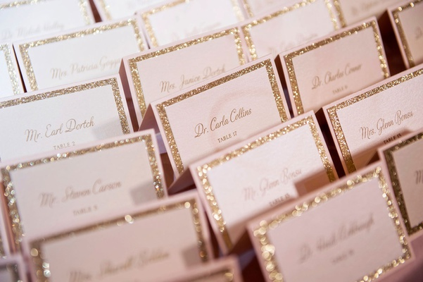 wedding escort cards gold glitter board calligraphy tables in black ink