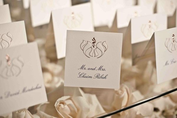 Seating cards on glass table with bed of roses