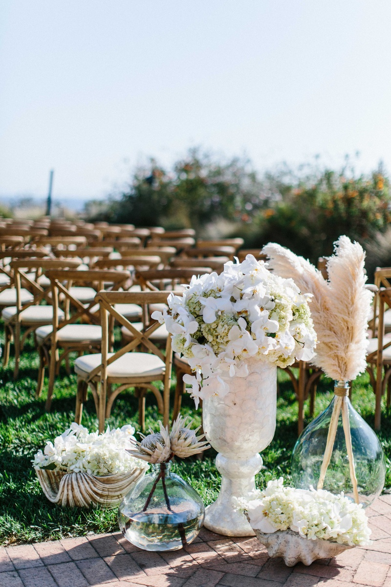Wedding ceremony at Terranea with white orchid, hydrangea, protea, botanicals feathers in glass vase