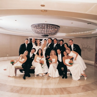 Bridesmaids in white dresses and groomsmen in black suits