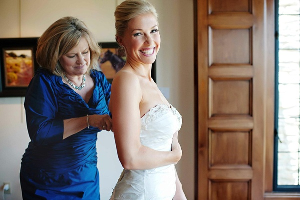 Mother of bride helps daughter into wedding dress