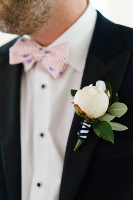 Groom with striped pink and white bow tie and blue whale with white peony boutonniere black white