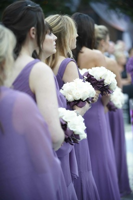 Bridesmaid bouquets with white roses and purple ribbon