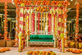 Tall gold structure wrapped with garlands of flowers