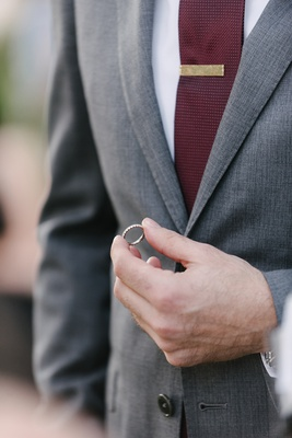 groom in grey suit and burgundy tie holding wedding ring during ceremony