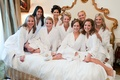 Bridesmaids in curlers and white robes and slippers