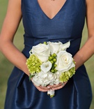 Bridesmaid in a sleeveless navy blue dress holds a bouquet of white roses, hydrangeas, calla lilies