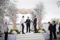 Groom in yarmulke and tallit with other groom on altar officiant cherry blossom trees pink flowers