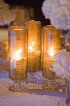 Wedding reception table with golden glass candle holders