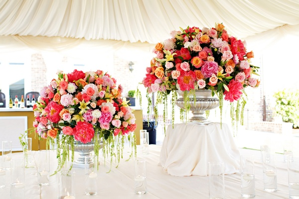 Wedding reception with silver urns filled with pink, white, and yellow flowers and greenery