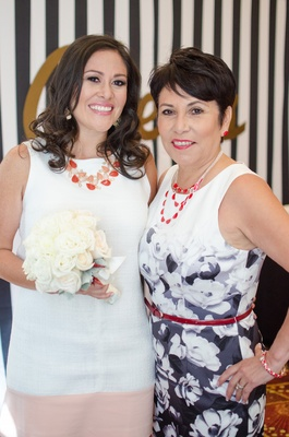 bride in a white dress with coral necklace white bouquet and mother in black and bridal shower
