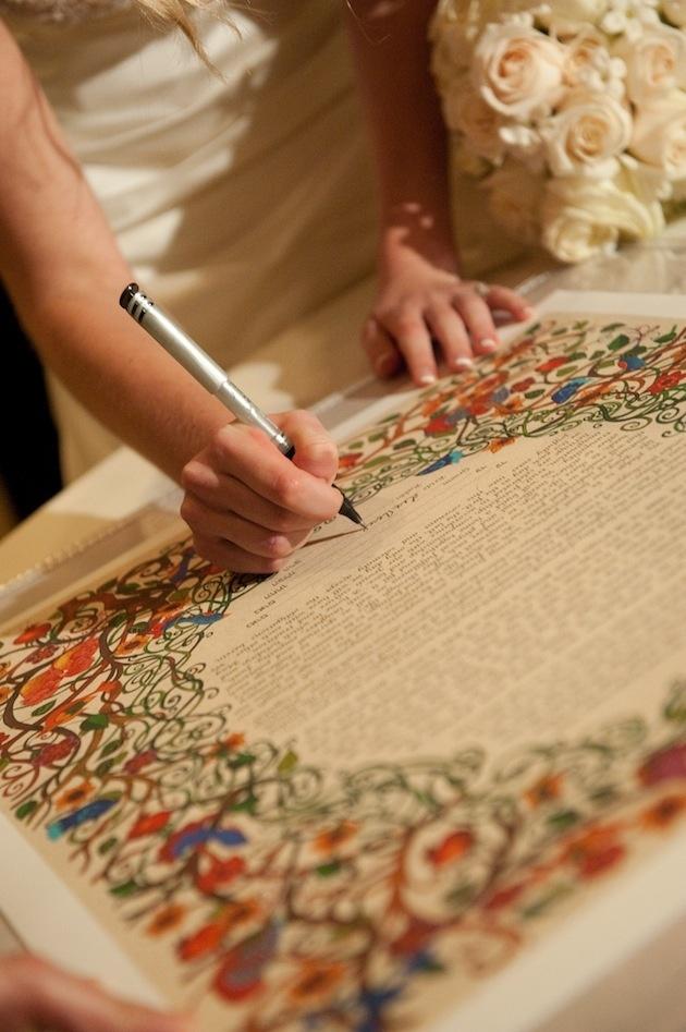 Bride signing colorful Jewish wedding ketubah