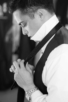 Black and white photo of man dressing his tie