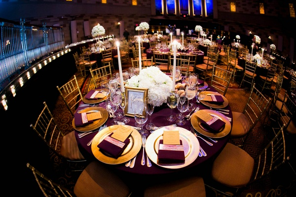 Wedding reception table at Gotham Hall with purple tablecloth and gold charger and white centerpiece