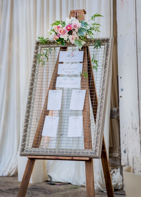 rustic wedding outside of barn wood easel chicken wire gold frame pink flowers greenery
