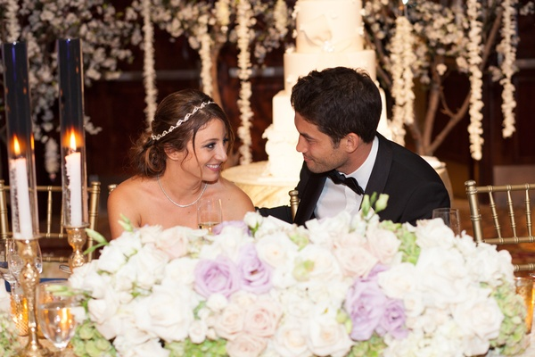 Bride with a crystal headband stares at groom in black tuxedo at head table with white & purple rose