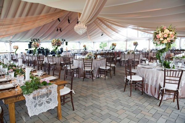 a whimsical tented space in an outdoor area with tables that featured a secret garden theme greenery