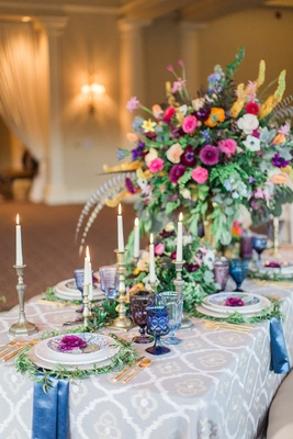 large centerpieces with a rainbow of flowers, mixed-metal candlesticks, colorful glassware