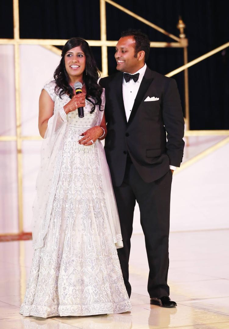 Bride in a beaded gown and groom in a black tuxedo at reception