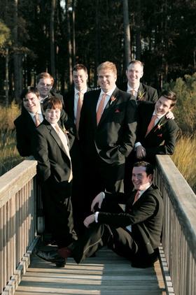 Groom and groomsmen in black suits with red orange ties