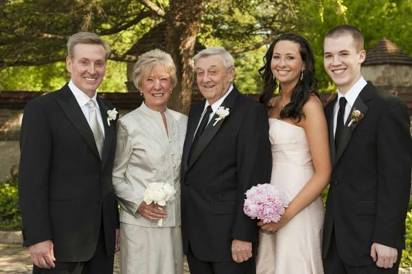 Groom in a black tuxedo with a silver tie and family